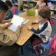 First grade boy reads his letter to a Marine in uniform