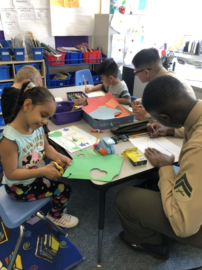 Two Marines in uniform draw pictures with crayons while 3 first graders cut out shapes and write cards.