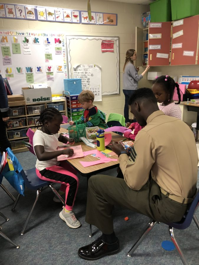 Three 1st grade students cut paper for cards and a Marines helps one cut.