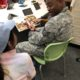 Student in blue hat reads a picture book to a Marine in fatigues