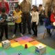 2 3rd grade girls and 1 3rd grade boy watch another student's robot executing its program. A Marine in uniform and the teacher watch from the side.
