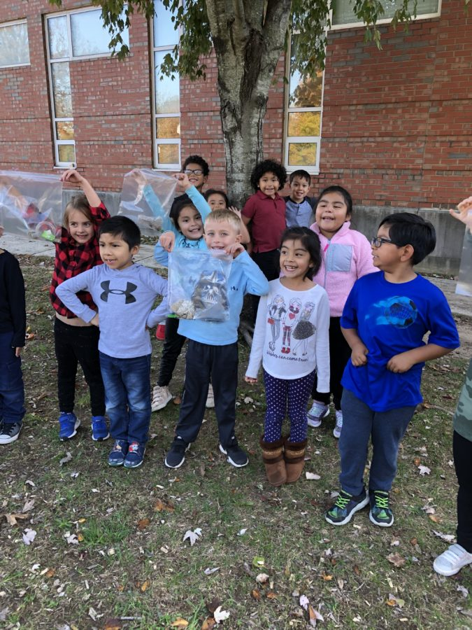Kindergarten students showing trash collected from playground