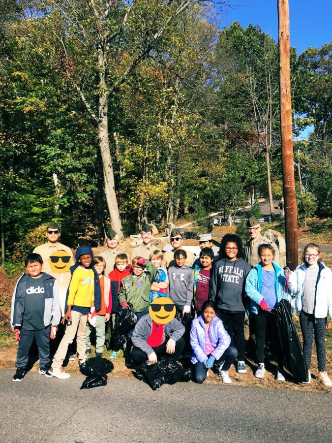 A group of fourth grade students and some Marines pose in front of the walking trail they just cleared.
