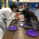 3 girls play a game transferring marchmellows between two plates using a straw
