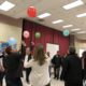 Adults stand in a circle and hit multicolored balloons into the air