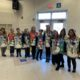 10 women dressed in gift bag costumes