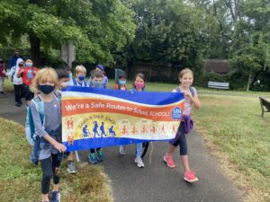 """Students outside walking holding a banner that reads """"We're a Safe Routes to School School!"""""""